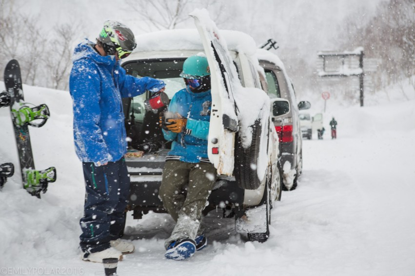 Snowboarders making hot tea with MSR Windstopper stove out of the back of the jeep after snowboarding in the Nito backcountry of Niseko, Japan.