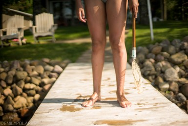 Young girl standing with wet bare feet on a dock with a fishing net in Wisconsin.