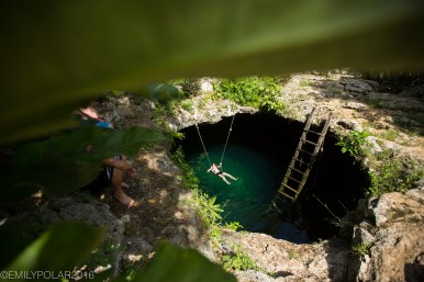 Boy hanging out in a swimming hole at Calaver Cenote, Tulum, Mexico