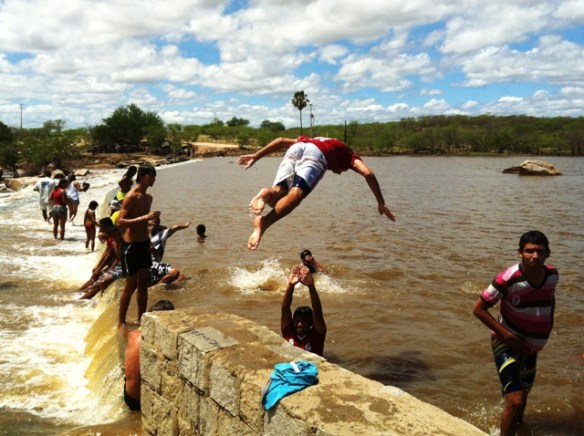 Menino comemora o fim da seca pulando na Barragem Pepeta, em Campo Grande