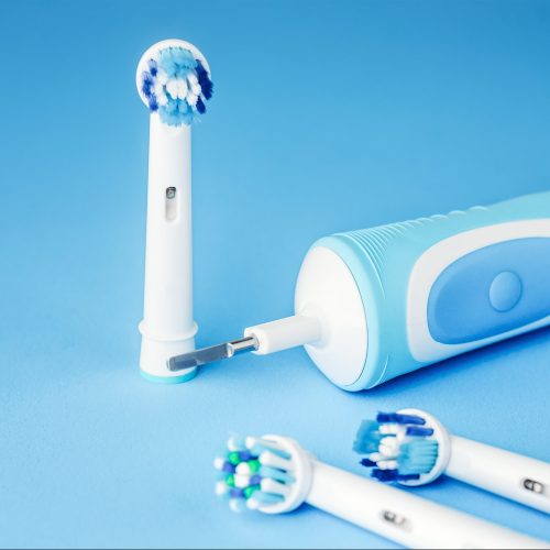 Modern electric toothbrush and spare heads on blue background, close up