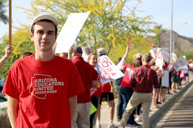 Arizona Educators United spokesman Noah Karvelis stands beside dozens of teachers and public education advocates protesting