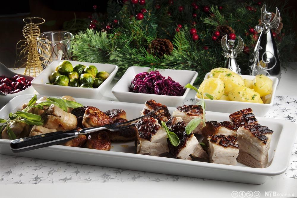 juleribbe, rosenkål, rødkål og kokte poteter lagt opp på fat på et bord med hvit duk og juledekorasjon.