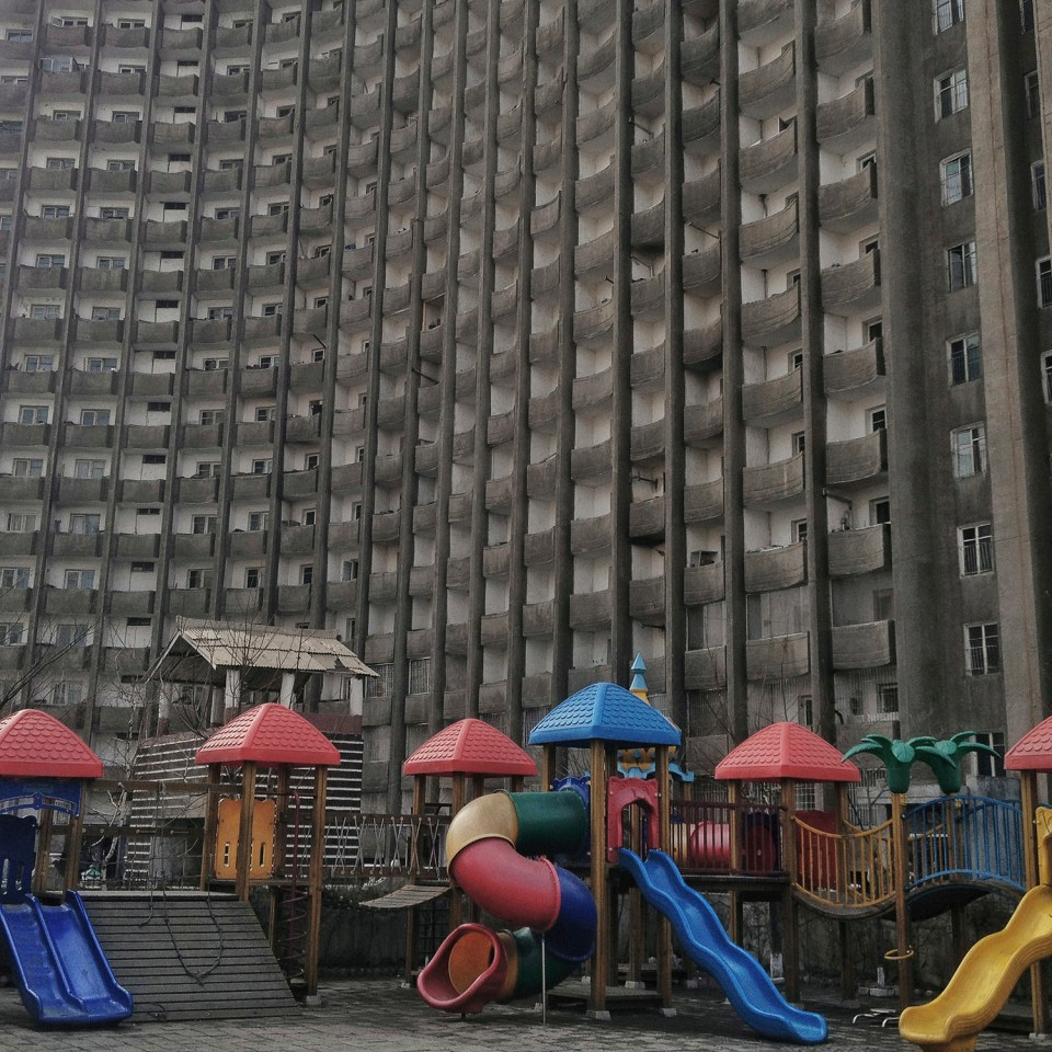 Playground equipment stand on a kindergarten school yard beneath an apartment housing building in Pyongyang, North Korea.