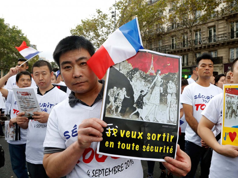 "A member of the Chinese commmunity in Paris holds a placard reading ""I want to go out in total security"" during a demonstration on September 4, 2016 in Paris, following the death of Zhang Chaolin and also calling for greater security measures. Several thousand ethnic Chinese staged a protest march in Paris on September 4 over the fatal mugging of a Chinese tailor last month, as crime against community members has spiralled. The protesters, almost all wearing white T-shirts reading ""Security for All"" and many waving French flags, rallied at the Place de la Republique in central Paris. Zhang Chaolin, who was 49, was set upon on August 7 by three thieves who tried to snatch a bag belonging to a friend of his. He died a few days later from his injuries. / AFP PHOTO / FRANCOIS GUILLOT"