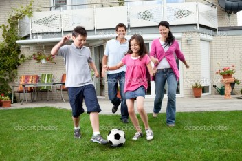 Cute kids playing football with their parents at backyard