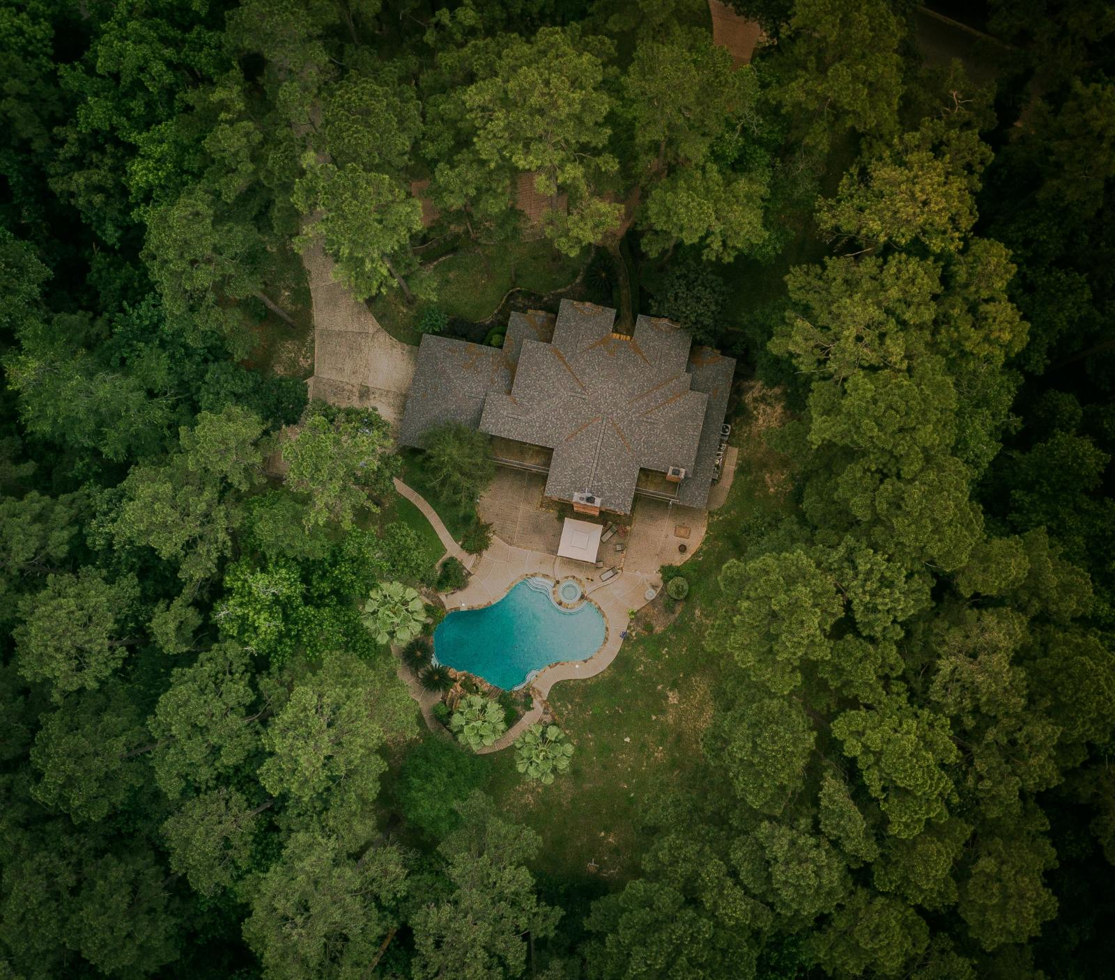 Aerial view, from drone cam, of forested area with a house in the middle.