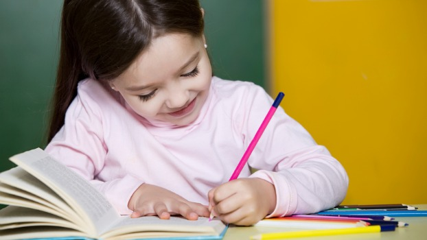 Child writing on book