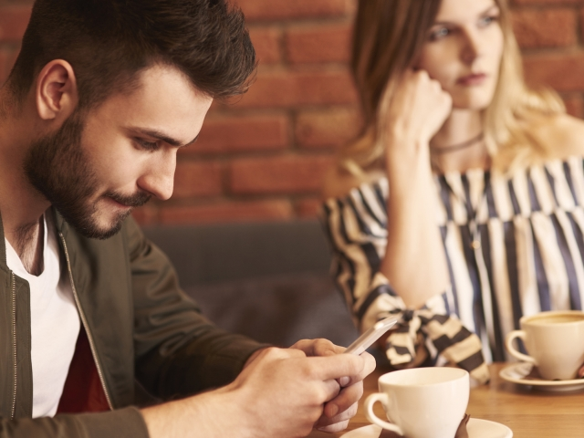 Man looking at his iPhone at a table with a woman