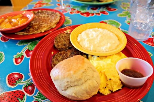 A dish of eggs, sausage, grits and a biscuit served at The Flying Biscuit