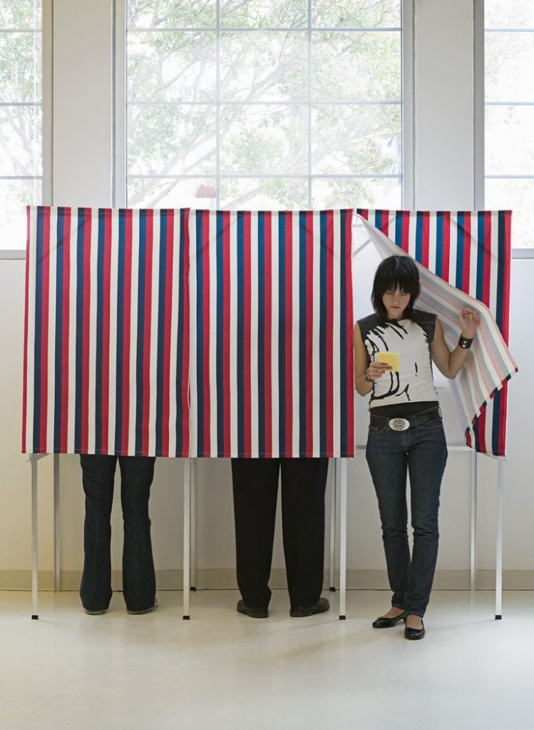 A young adult leaving a voting booth