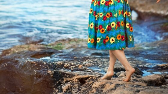 woman in floral dress walking barefoot along the beach