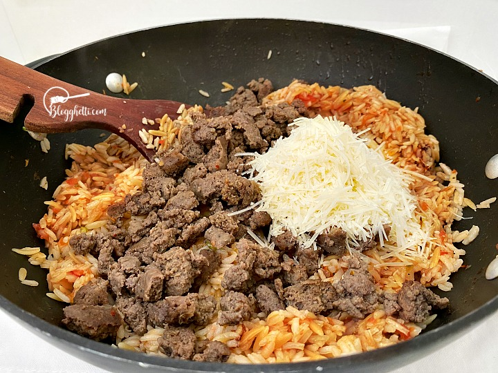 adding the sausage and cheese to rice filling for stuffed peppers