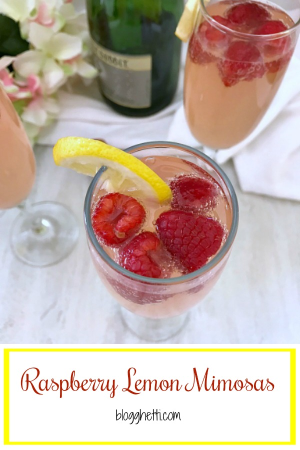 Raspberry Lemon Mimosas in champagne flutes with the fresh fruit in the glasses
