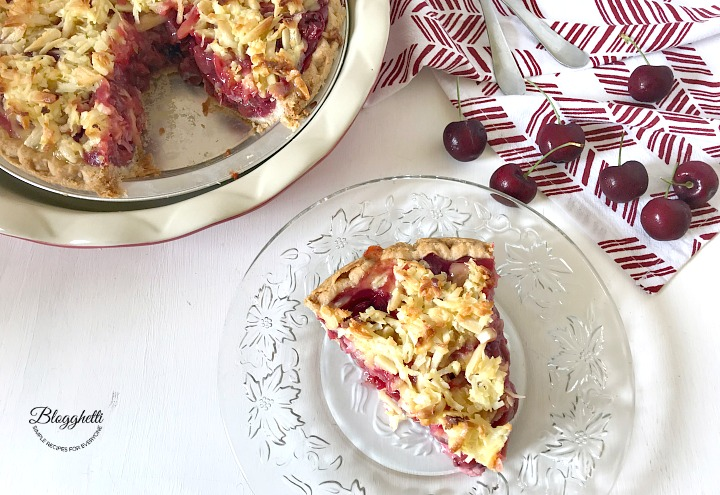 Slice of Macaroon Cherry Pie with the pie plate in the background