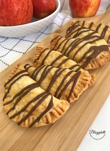 Chocolate Glazed Apple Hand Pies on a wooden platter with apples in the background