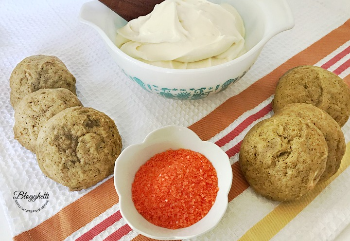 Pumpkin Cookies with bowl of homemade cream cheese frosting and orange sugar sprinkles