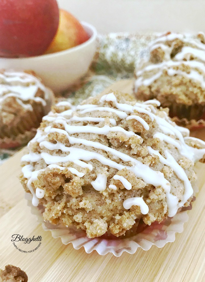 closeup of an Apple Coffee Cake Muffin with a bowl of apples in the background