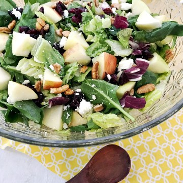Apple Cranberry Pecan Salad in crystal bowl with a small wooden spoon