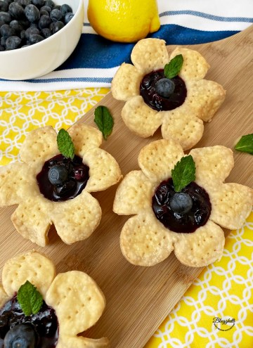 Blueberry flower tarts with mint leaf for garnish