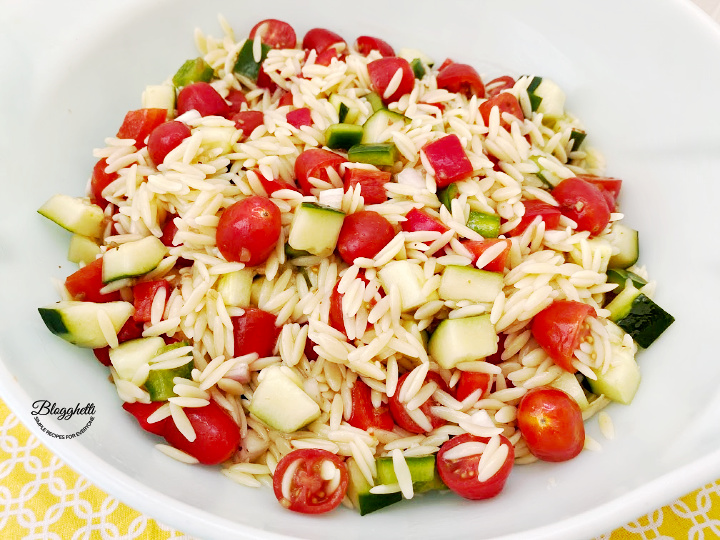 mixing orzo pasta salad with dressing