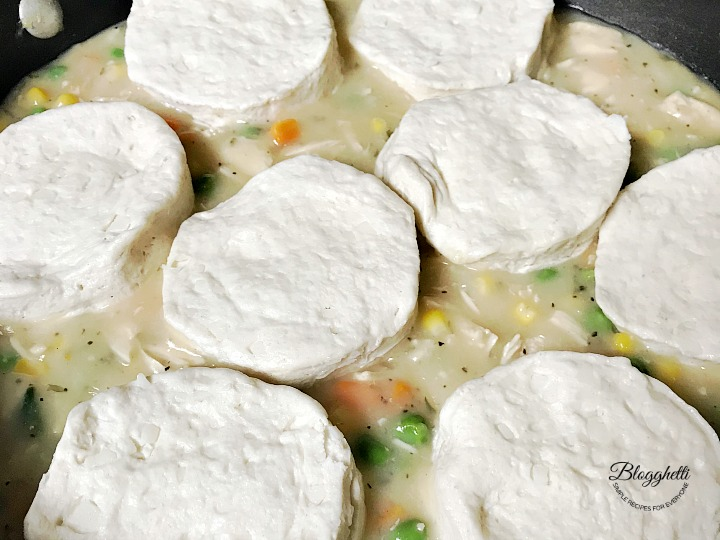 topping the pot pie mixture with biscuits