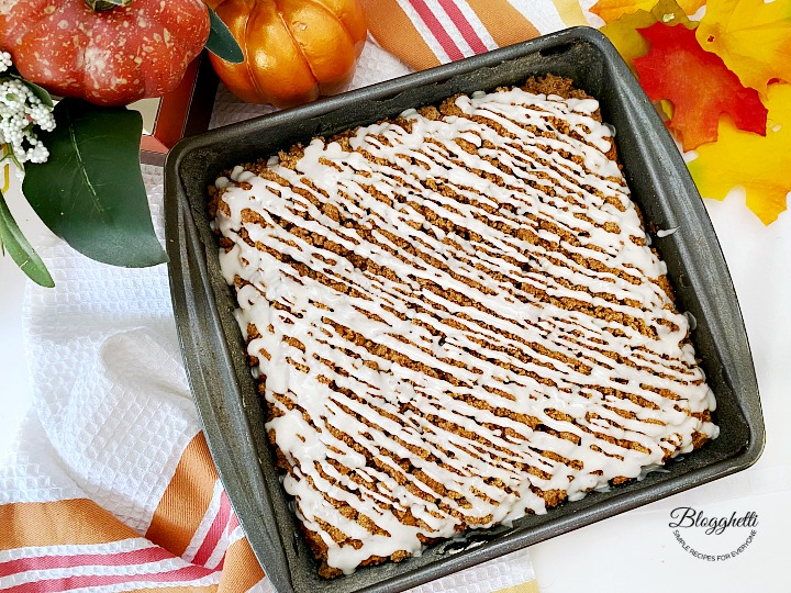 glazed pumpkin spice coffee cake with fall decor in background