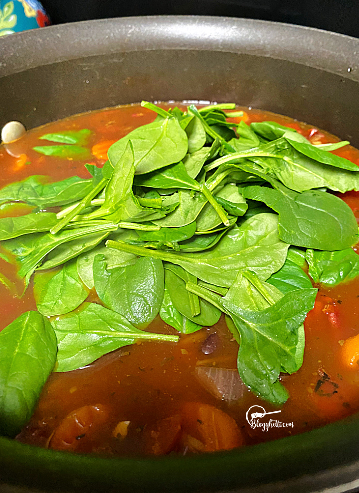 adding spinach to the vegetable soup