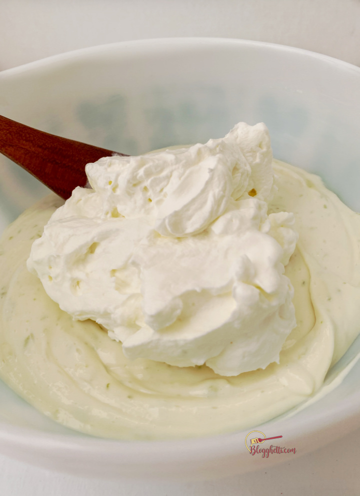 adding whipped cream to lime cream cheese mixture in bowl