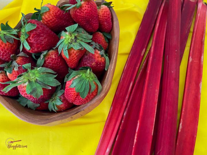 bowl of strawberries and stalks of rhubarb