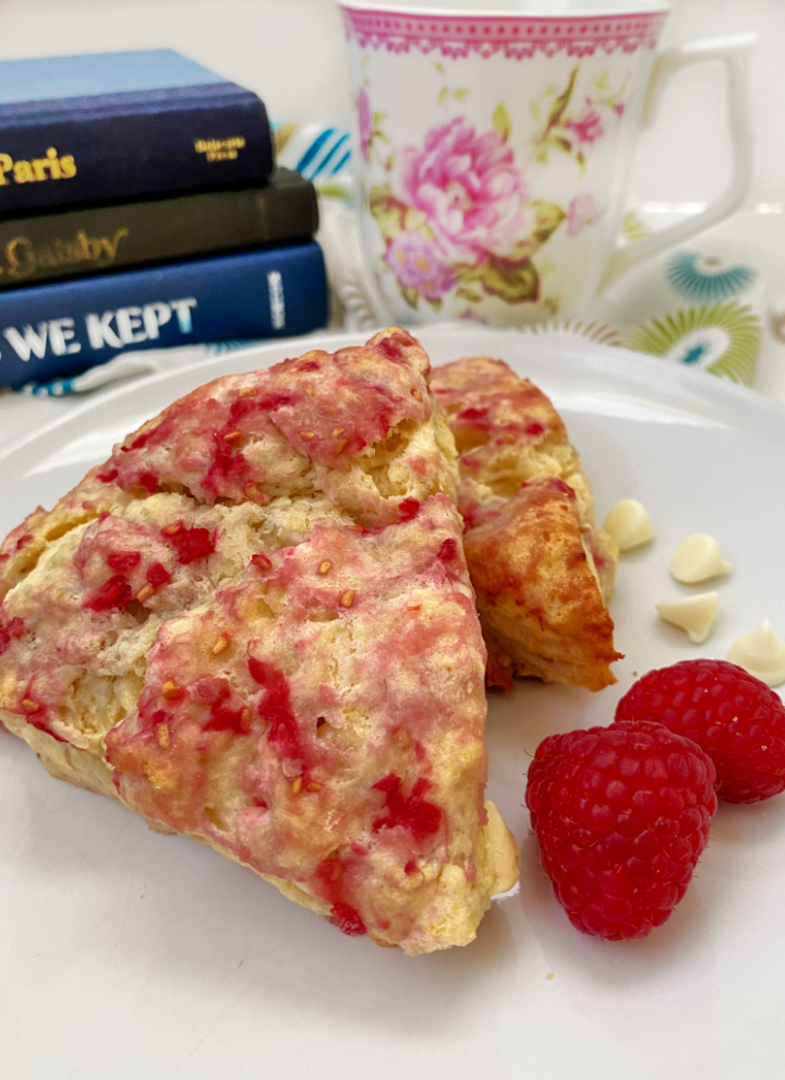coffee cup with rasp scones with books in the background