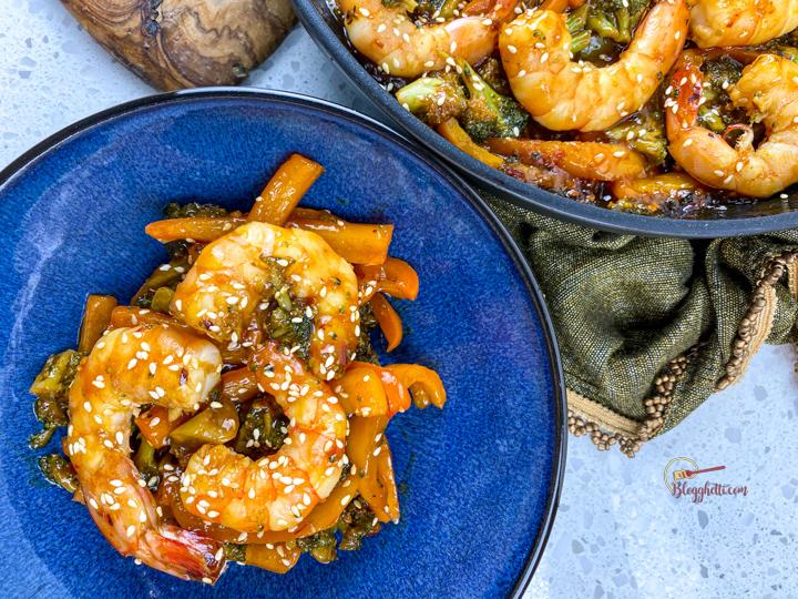 spicy honey garlic shrimp skillet on blue plate