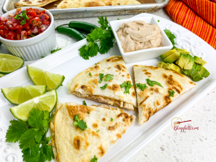 serving platter with rotisserie chicken quesadilla and toppings