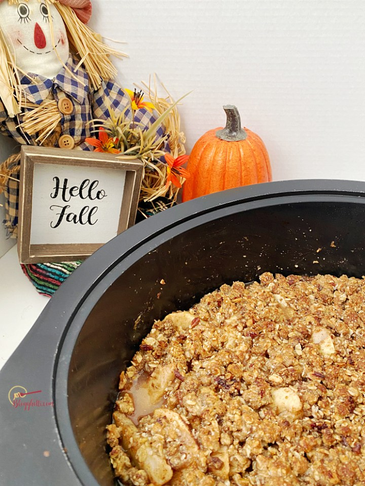 slow cooker apple pear crisp with Hello Fall sign in background