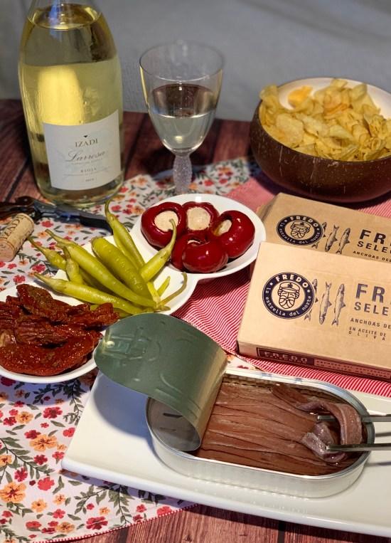 Aperitivo con anchoas, tomates secos, piparras, tomates rellenos, patatas fritas y copa de vino y botella de Larrosa Blanca de Bodegas Izadi
