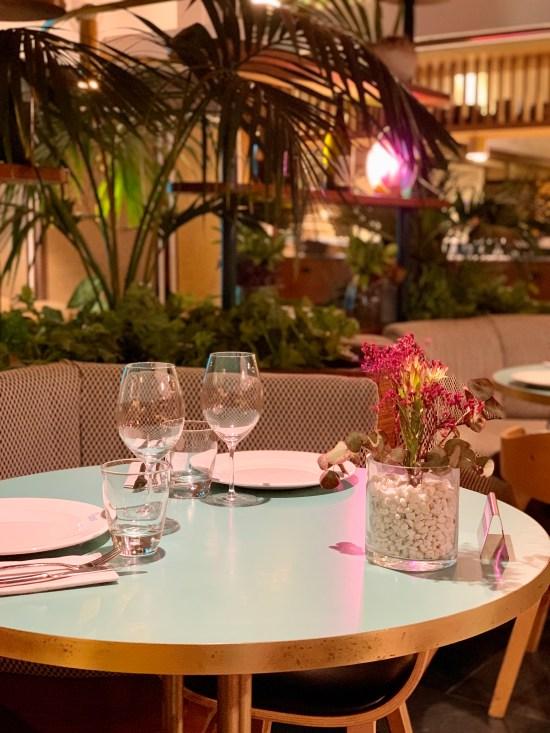 Comedor de Can Fisher, se ven unas flores en su florero, unas copas y su platos a punto para comer. También la decoración del local