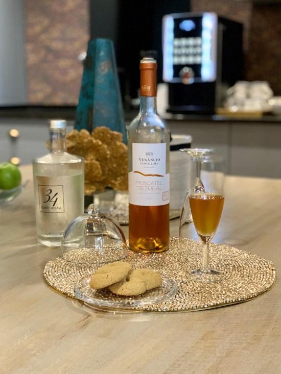 copa de moscatel de Setúbal, botella de vino, botella de agua, dulces