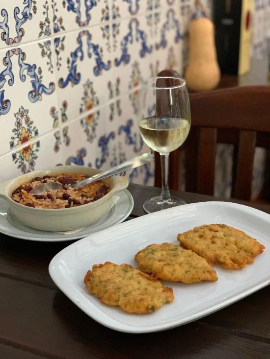filetitos de bacalao con su arroz de acompañamiento y copa de vino blanco