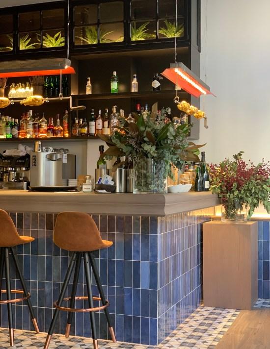 barra de azulejos y mostrador de madera, taburetes altos, flores, lámpara