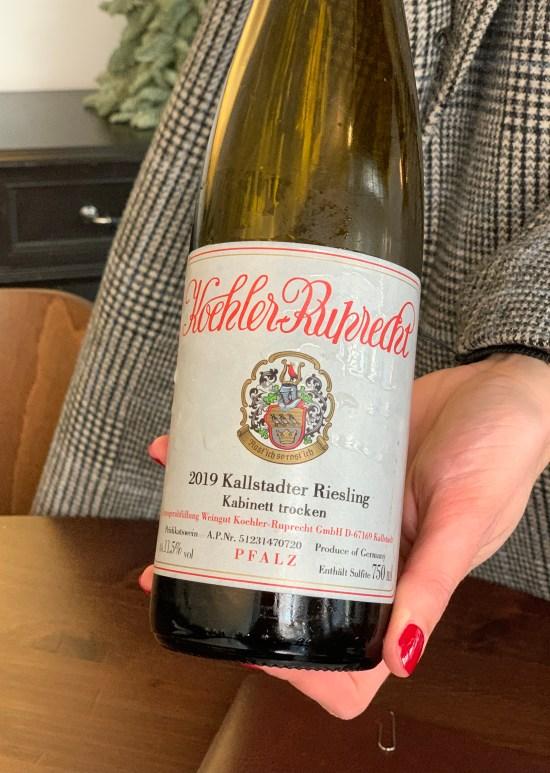 Botella de vino Riesling, cogida con una mano