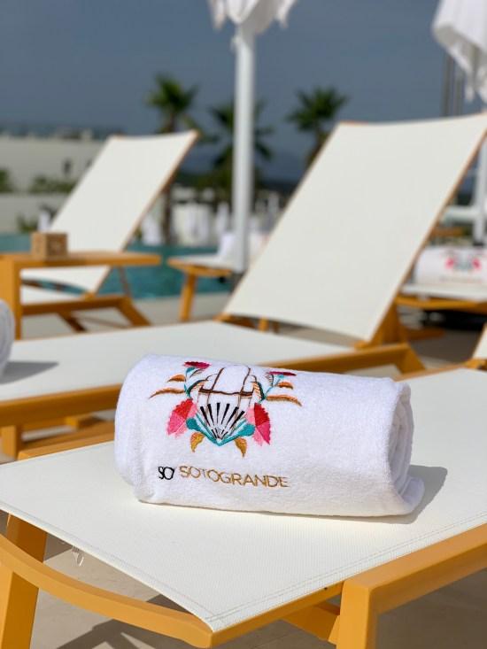 toalla con el emblema del hotel y hamacas