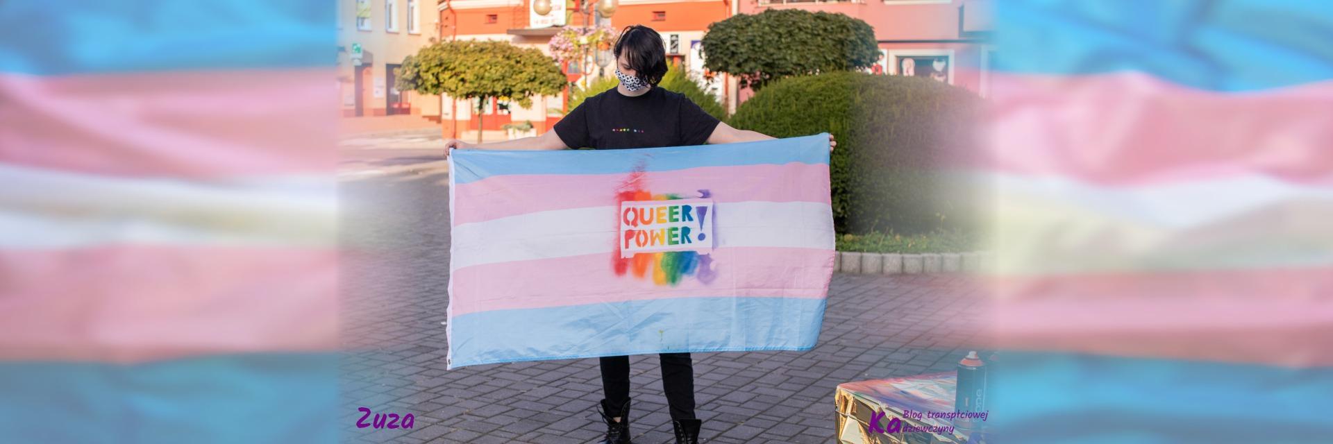 Zuza, ubrana na czarno, na koszulce kolorowe gwiazdki 5 i 3 szt., trzyma flagę trans z tęczowym napisem Queer Power!