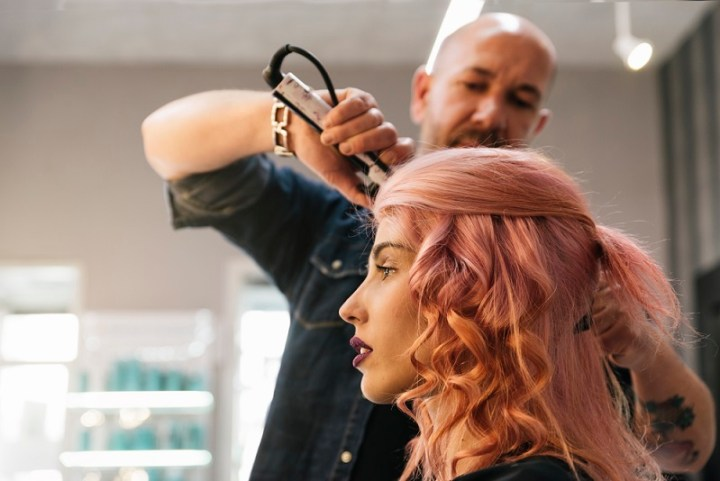 Beautiful woman getting haircut by hairdresser in the beauty salón.