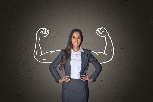 38200116 - conceptual smiling young businesswoman standing in front gray gradient background with arm muscles drawing, emphasizing power.