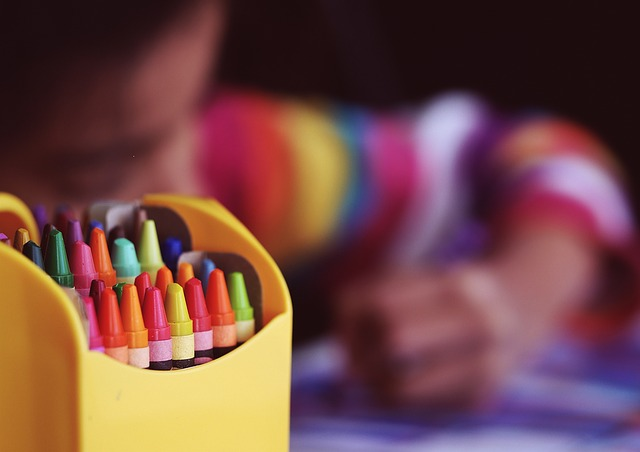 crayons in box with child drawing
