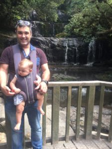 man holding baby in carrier at waterfall