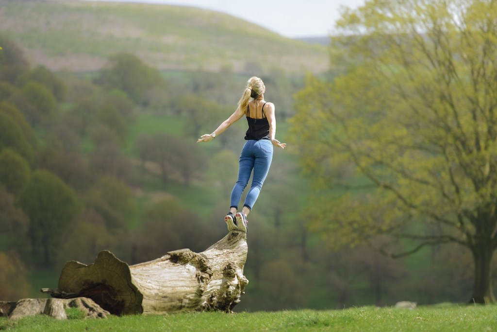 a woman balancing on a tree trunk