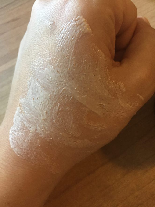 pink clay mask spread on hand