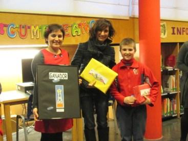 El ganador y su profesora recibiendo los premios.