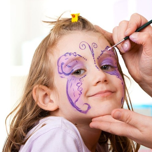 Little smiling girl having face painted on birthday party.